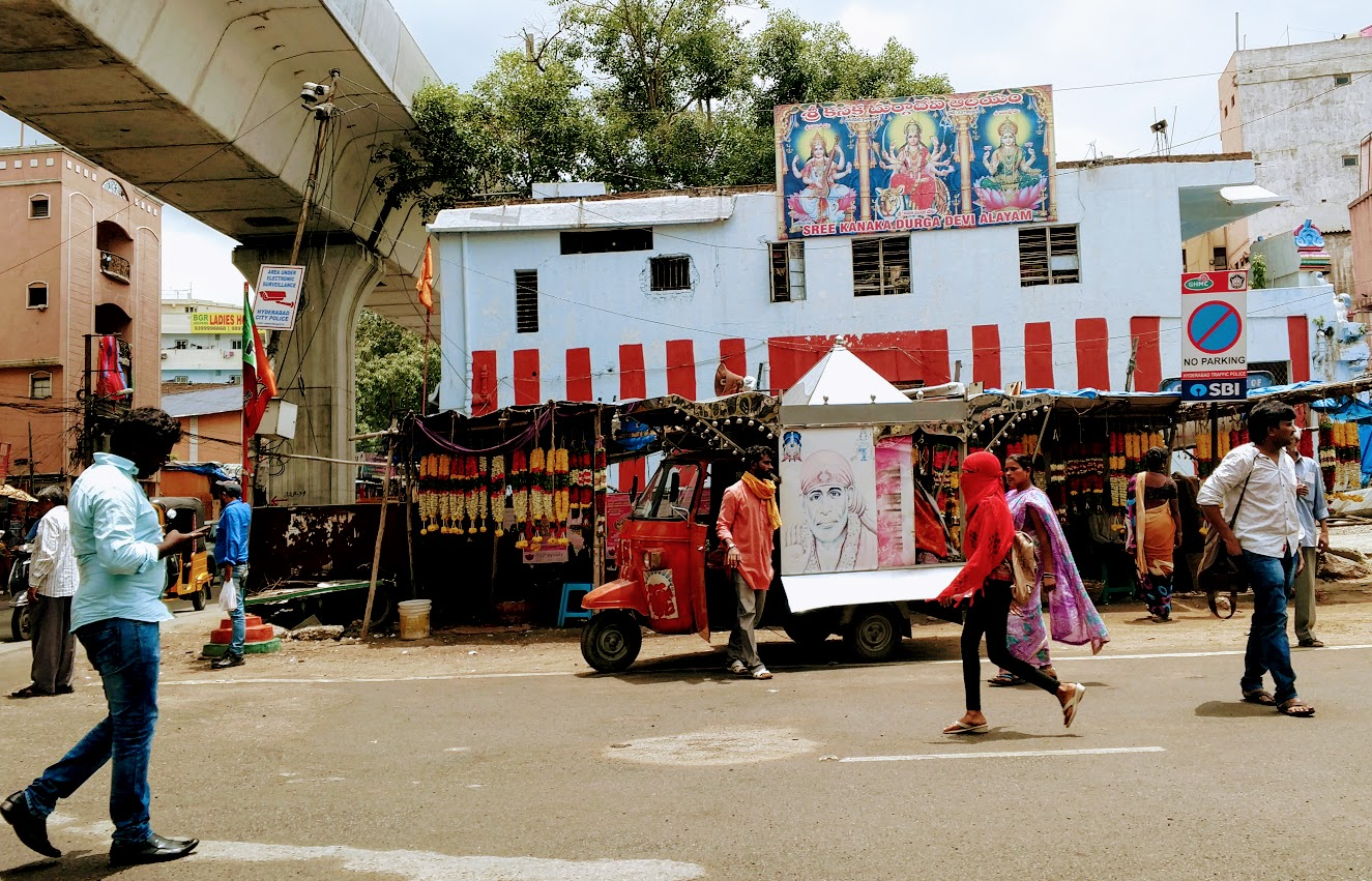The roaming temple scooter is in front of a flower garland vendor. On the right you'll see both an Indian woman wearing a sari and a second young woman wearing Western dress and a full face veil.