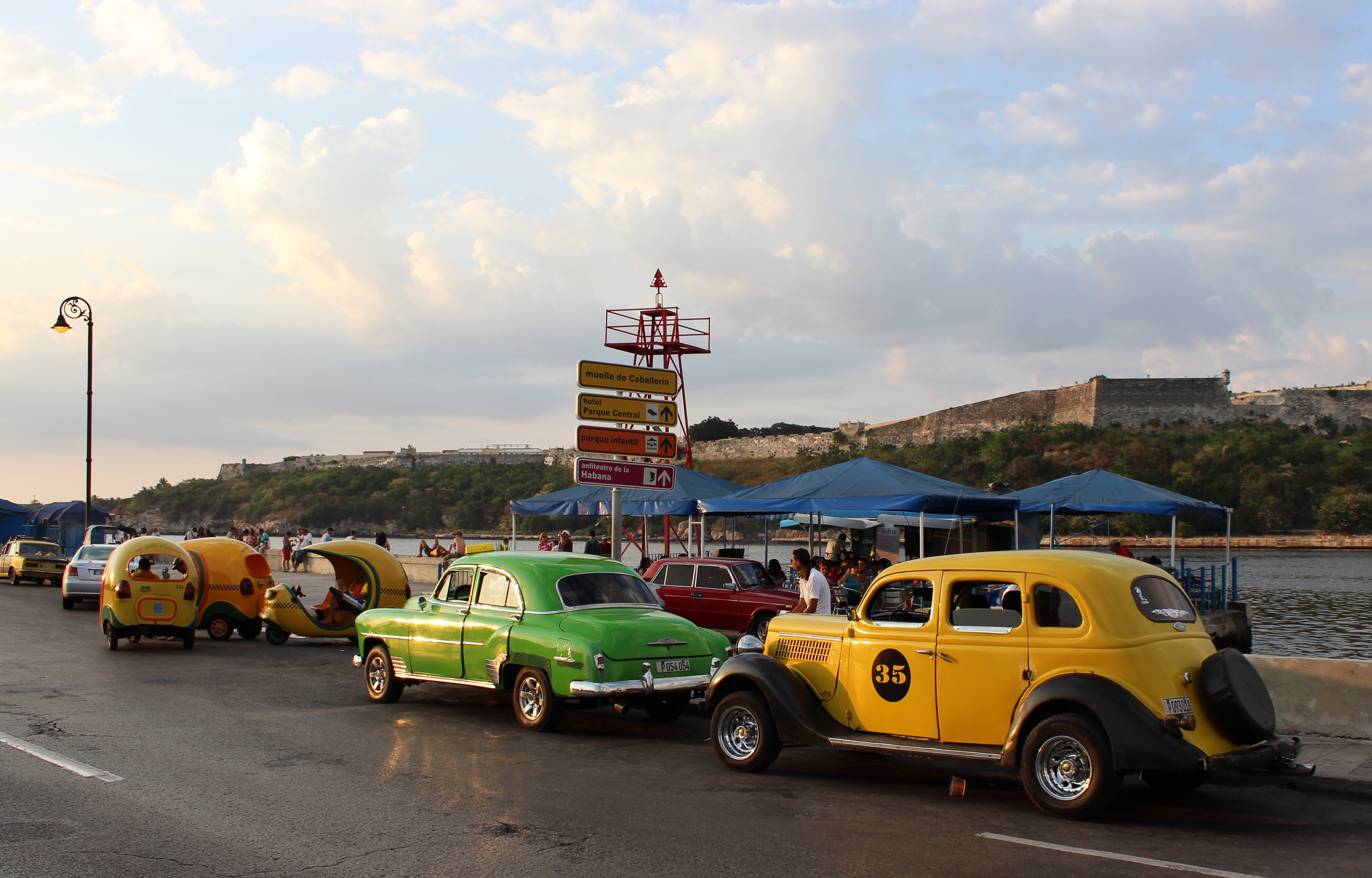 Coco cabs and vintage cars for hire wait for passengers.