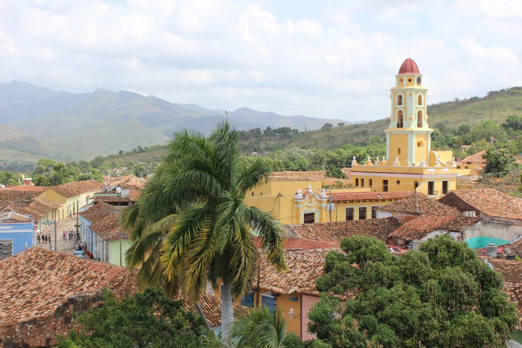 The yellow church faces the Plaza Mayor while the Escambray Mountains can be seen in the distance.