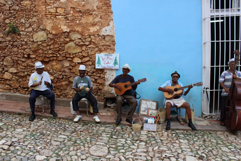 Street musicians play Cuban son music outside a restaurant in Trinidad, Cuba.