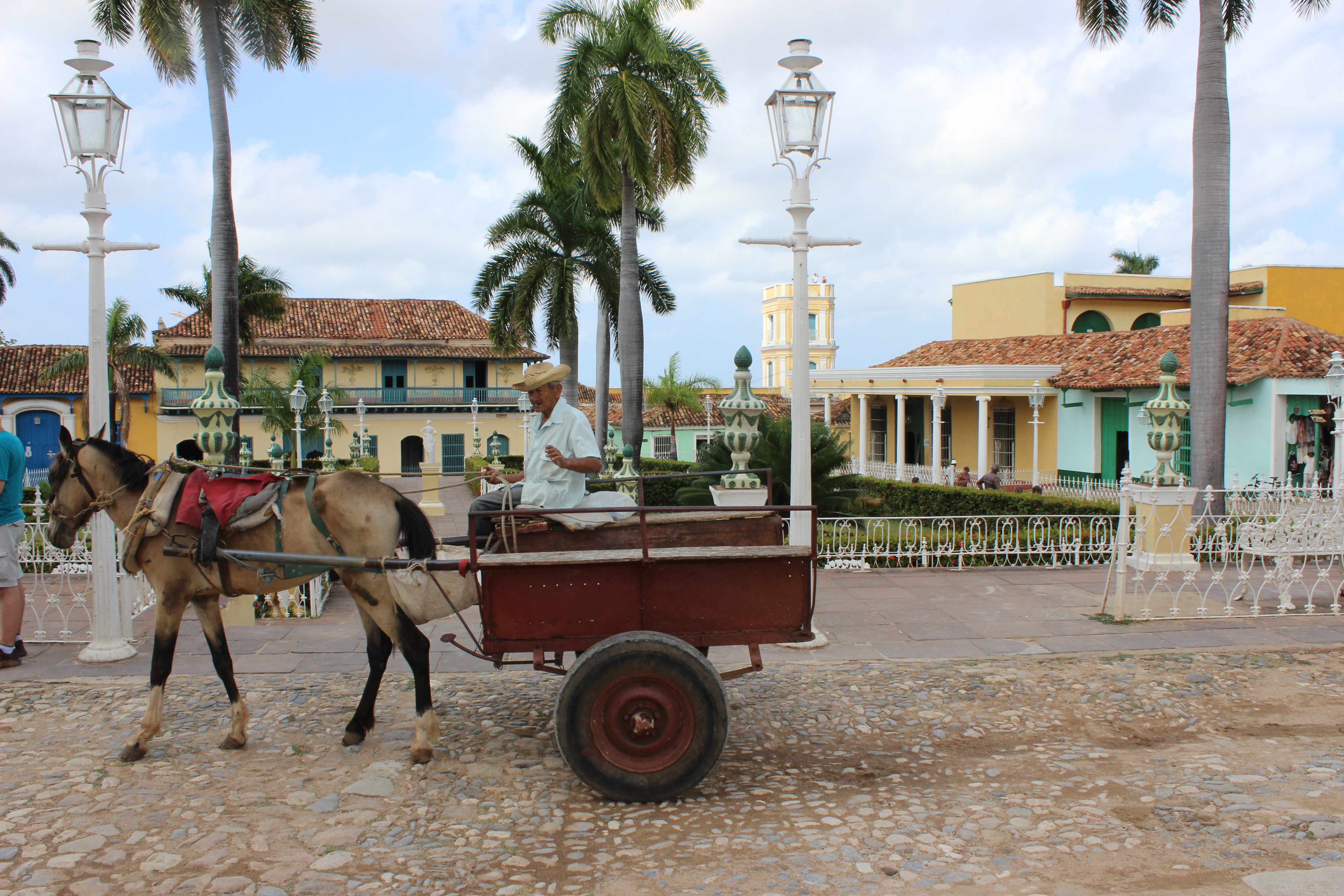 A guajiro, or rural man drives a horse drawn carriage past the Plaza Mayor in Trinidad, Cuba.