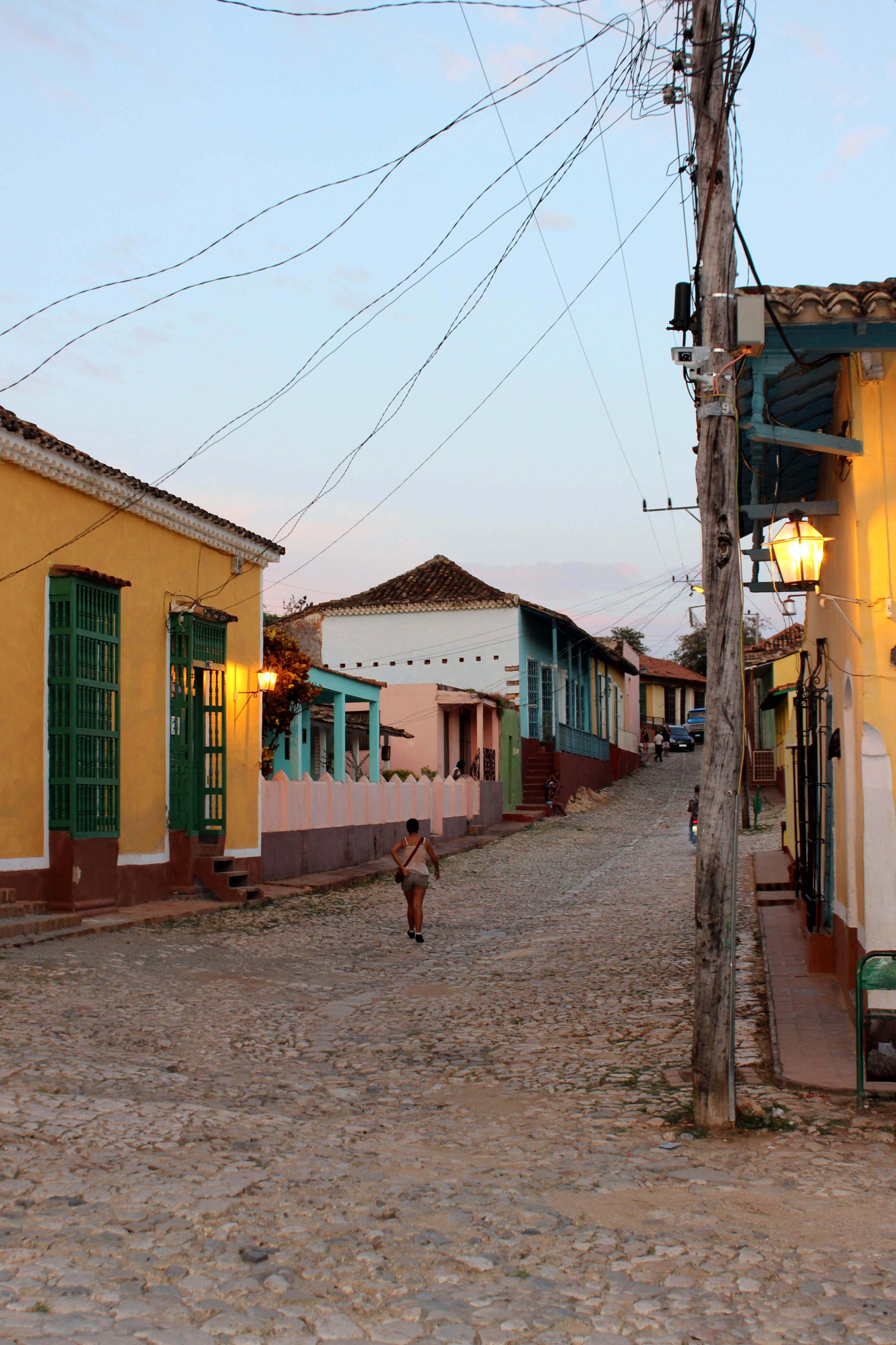 In Cuba's five hundred year old town of Trinidad, a woman walks home at dusk.