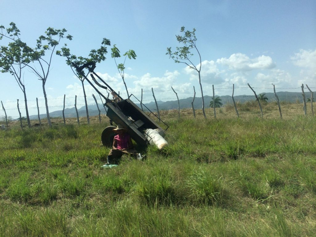 An image of a A farmer rests under a wooden plow in a field outside Trinidad in Cuba's verdant Valle de Los Ingenios.